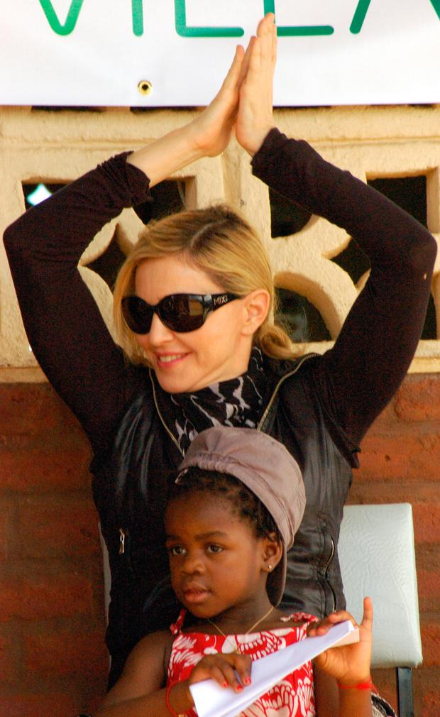 US artist Madonna and her adopted daughter Mercy James sit at a community school funded by her during a visit to Gumulira Millenium villages in Mchinji, west of the capital, Lilongwe, on April 5, 2010 .