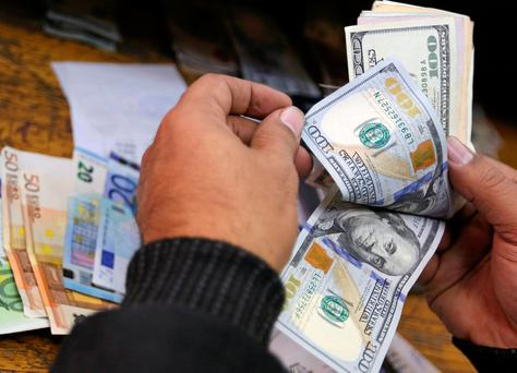 A man counts US dollars and Euros at a money exchange office in central Cairo, Egypt