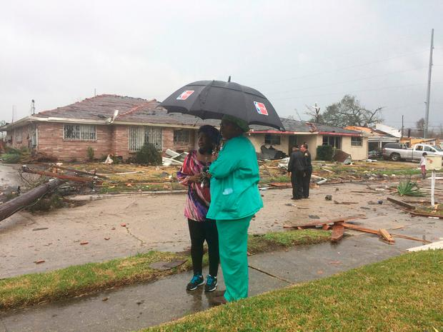 Linda Pierre, left, and April Williams look around the east New Orleans neighborhood after a tornado touchdown, Tuesday, Feb. 7, 2017. (AP Photo/Gerald Herbert)