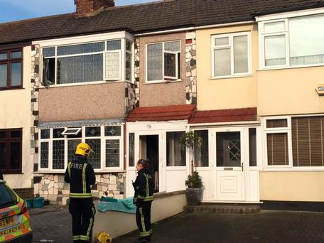 A firefighter and police officer outside the property in Laburnum Avenue, Hornchurch, the scene of a fire. Photo: Ann-Marie Abbasah