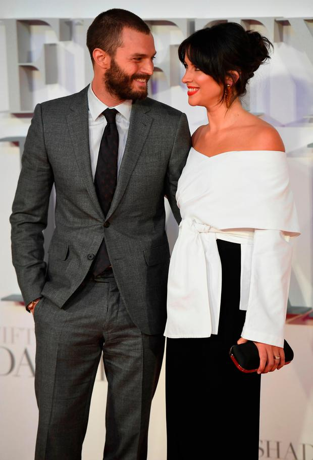 Jamie Dornan (L)and his wife English actress Amelia Warner pose on the red carpet upon arrival at the UK premiere of Fifty Shades Darker in London