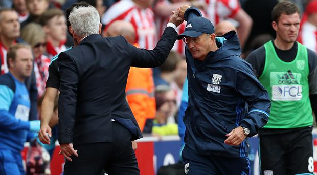 STOKE ON TRENT, ENGLAND - SEPTEMBER 24: An awkward hand shake for manager Mark Hughes of Stoke City and manager Tony Pulis head of West Bromwich Albion at the end of the match that finished 1-1 during the Premier League match between Stoke City and West Bromwich Albion at Bet365 Stadium on September 24, 2016 in Stoke on Trent, England. (Photo by Adam Fradgley - AMA/WBA FC via Getty Images)