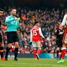 Arsenal's Alexis Sanchez is shown a yellow card by referee Mark Clattenburg