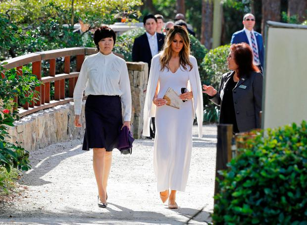 U.S. First Lady Melania Trump (C) and Akie Abe (L), wife of Japanese Prime Minister Shinzo Abe, listen to Park Administrator Bonnie White Lemay, as they tour Morikami Museum and Japanese Gardens in Delray Beach, Florida