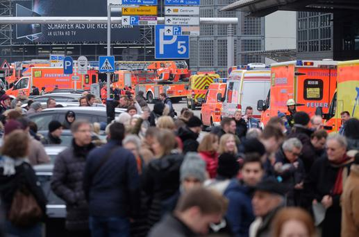 Travellers wait outside the Hamburg, northern Germany, airport Sunday, Feb. 12, 2017 after after several people were injured by an unknown toxic that likely spread through the airportsÄô air conditioning system. (Axel Heimken/dpa via AP)