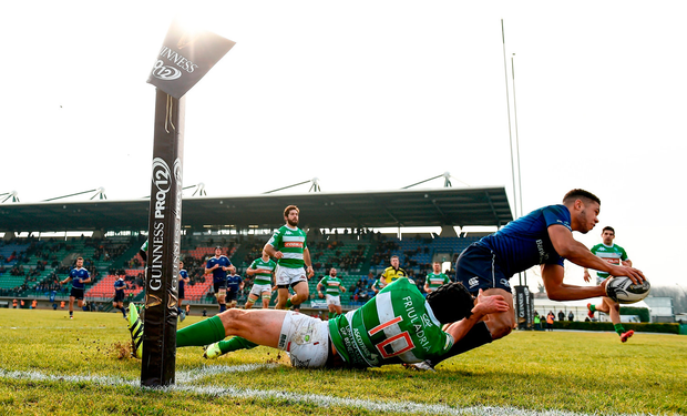 Leinster's Adam Byrne goes over to score his side's fourth try despite the attention of Treviso's Ian McKinley Photo: Stephen McCarthy/Sportsfile