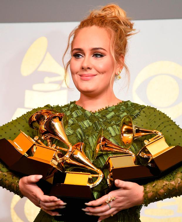 Adele poses in the press room with her trophies, including the top two Grammys of Album and Record of the Year for her blockbuster hit