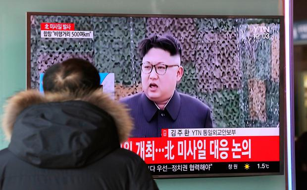 A man watches a TV news program showing a file footage of North Korean leader Kim Jong Un with letters reading: