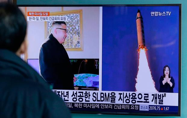 A man watches a TV news program showing photos published in North Korea's Rodong Sinmun newspaper of North Korea's