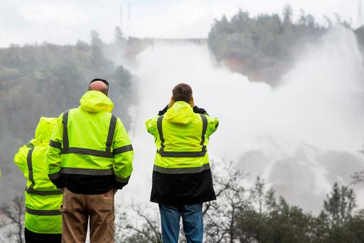 California Department of Water Resources personnel monitor water flowing through a damaged spillway on the Oroville Dam in Oroville, California, U.S. REUTERS/Max Whittaker/File Photo