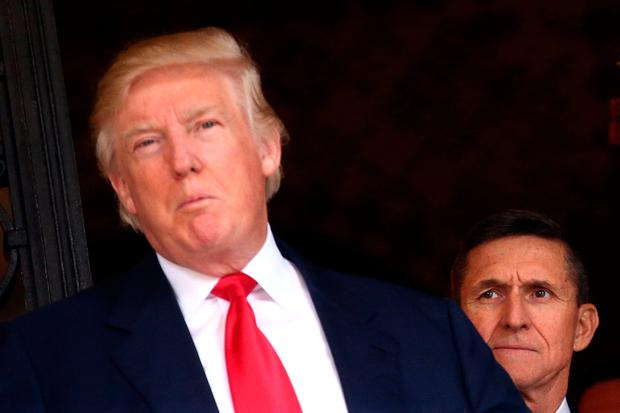 FILE PHOTO: U.S. Army Lieutenant General Michael Flynn looks at U.S. President-elect Donald Trump as he talks with the media at Mar-a-Lago estate where Trump attends meetings, in Palm Beach, Florida, U.S., December 21, 2016. REUTERS/Carlos Barria/File Photo