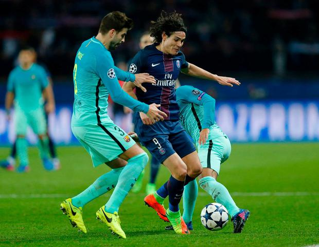 Paris Saint-Germain's Edinson Cavani in action with Barcelona's Gerard Pique. Photo: Benoit Tessier / Reuters