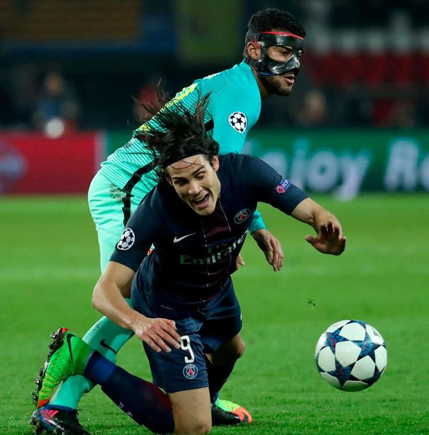 Paris Saint-Germain's Edinson Cavani in action with Barcelona's Rafinha. Photo: Christian Hartmann/Reuters