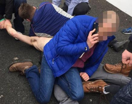 Brave members of the public pin the bare-chested man to the ground (Photo: Independent.ie)