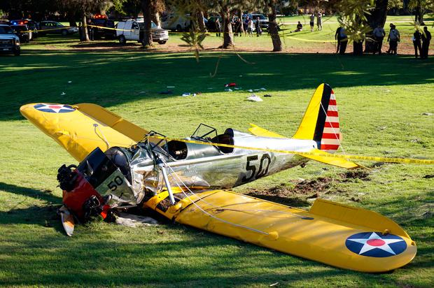 In this March 5, 2015 file photo, a World War II-era trainer airplane rests on the ground after actor Harrison Ford crash-landed it after reporting engine failure on the Penmar Golf Course in the Venice area of Los Angeles. (AP Photo/Damian Dovarganes, File)