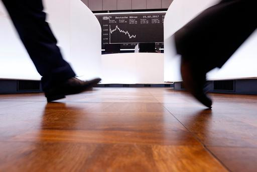 A trader walks past the German DAX Index board on the trading floor at the Frankfurt stock exchange in Frankfurt