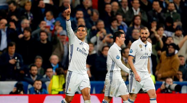 Real Madrid's Casemiro, left, celebrates after scoring his side's third goal during the Champions League round of 16, first leg, soccer match between Real Madrid and Napoli at the Santiago Bernabeu stadium