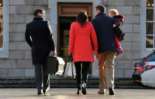 Garda whistleblower Keith Harrison (holding his daughter) and his partner Marissa Simms going into Leinster House for meetings yesterday. Photo: Tom Burke