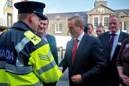 Taoiseach Enda Kenny (centre) shaking hands for the first time with Garda whistleblower Sgt Maurice McCabe (left) in Mullingar, Co Westmeath, in 2014