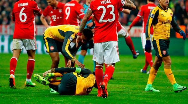 Laurent Koscielny lays injured during the UEFA Champions League round of 16 match between FC Bayern Munich and Arsenal