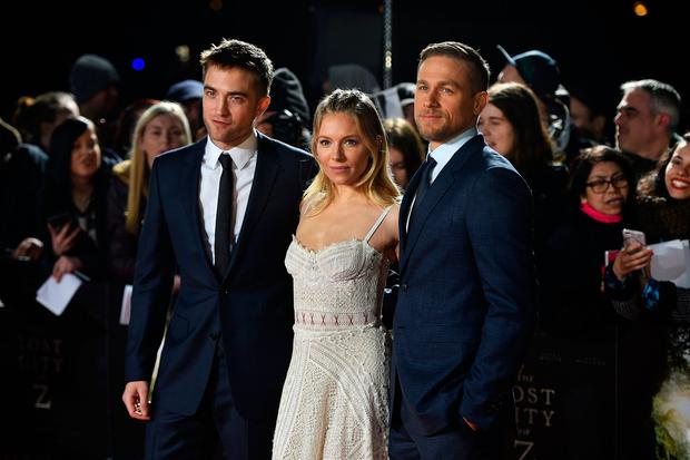 Actors Robert Pattinson, Sienna Miller and Charlie Hunnam pose at the premiere of the film