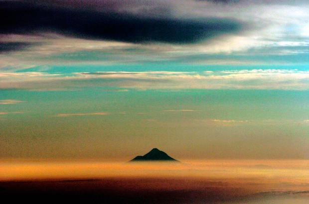 Mt Taranaki pokes its top through a layer of clouds as the sun sets in his photo taken from an airplane in New Zealand, Friday, January 28th, 2005 Phil Walter/Getty Images