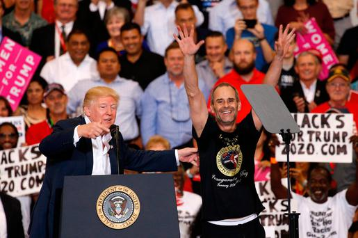 U.S. President Donald Trump invites a supporter onstage with him during a