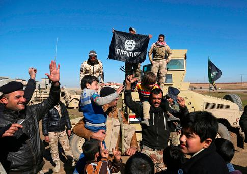Iraqi Army soldiers celebrate with residents of liberated neighborhoods as they hold upside down a flag of the Islamic State group, in the eastern side of Mosul, Iraq. (AP Photo/Khalid Mohammed, File)