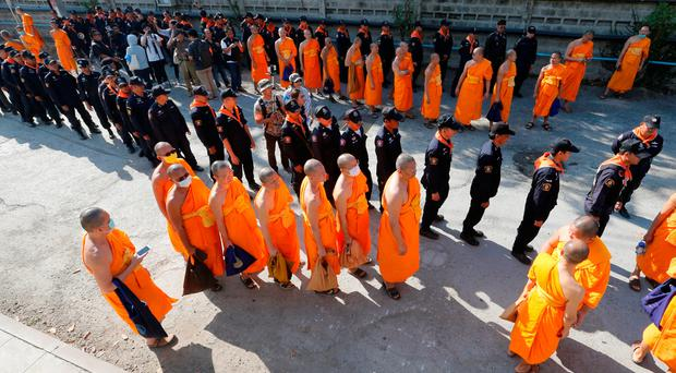 Policemen and Buddhist monks walk inside Dhammakaya temple to search for a fugitive Buddhist monk in Pathum Thani province, Thailand
