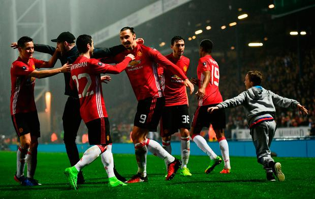 A young fan runs onto the pitch as Zlatan Ibrahimovic of Manchester United (9) celebrates with team mates