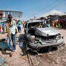 A man walks past a wrecked vehicle after a blast in a market in the capital Mogadishu. Photo: Abdi Warsameh/AP Photo