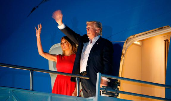 U.S. President Donald Trump and first lady Melania Trump wave from Air Force One after a