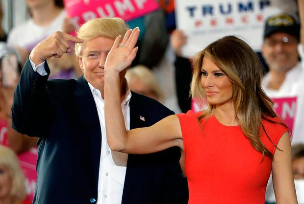 President Donald Trump points to his wife, first lady Melania Trump during a campaign rally Saturday, Feb. 18, 2017, at Orlando-Melbourne International Airport, in Melbourne, Fla. (AP Photo/Chris O'Meara)