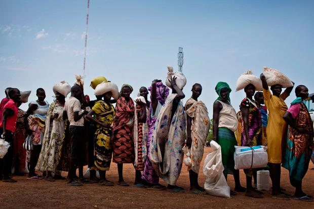 In this photo taken Wednesday, Oct. 19, 2016 and released by UNICEF, women who fled fighting in nearby Leer in recent months, queue for food aid at a food distribution made by the World Food Programme in Bentiu, South Sudan. (Kate Holt/UNICEF via AP)