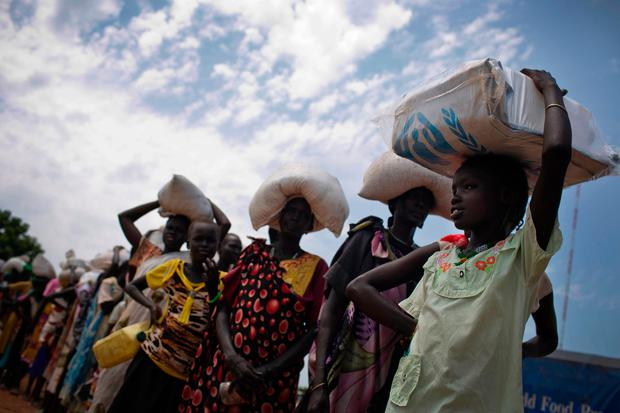 In this photo taken Wednesday, Oct. 19, 2016 and released by UNICEF, a young girl who fled fighting in nearby Leer in recent months, queues for food aid at a food distribution made by the World Food Programme in Bentiu, South Sudan. (Kate Holt/UNICEF via AP)