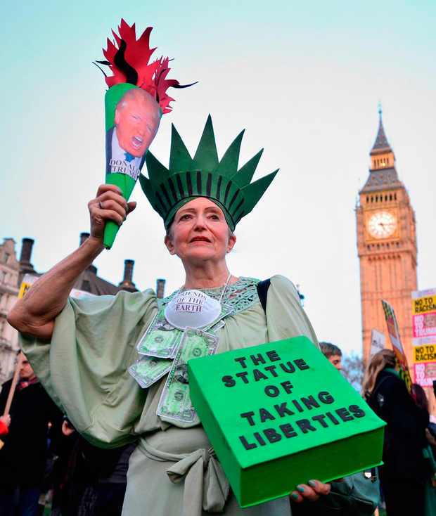 A demonstrator takes part in a protest against US President Donald Trump outside the Houses of Parliament in London, yesterday Photo: Dominic Lipinski/PA Wire