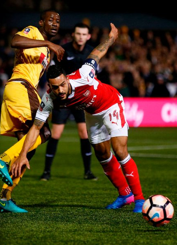 Arsenal's Theo Walcott keeps his balance as he gets past Sutton United's Kevin Amankwaah. Photo: Reuters