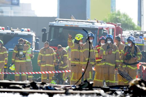 Fire crew at the scene where a light plane crashed into the back of a building at Essendon airport in Melbourne, Australia, February 21, 2017. AAP/Joe Castro/via REUTERS