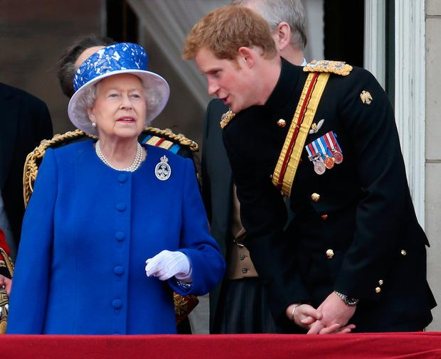 Prince Harry chats to Queen Elizabeth II on the balcony of Buckingham Palace during the annual Trooping the Colour Ceremony on June 15, 2013 in London, England.