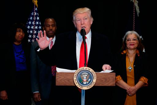 US President Donald Trump speaks at the National Museum of African American History and Culture, in Washington DC, flanked by, from left, Candy Carson; Dr Ben Carson, Mr Trump's pick for Housing Secretary; and Alveda King, niece of Dr Martin Luther King Jr. Photo: Evan Vucci/AP