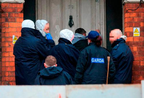 Gardai investigating the death of Gary O'Brien prepare to enter a property on the North Circular Road. Photo: Collins