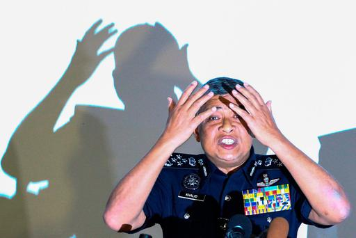 Malaysia's Royal Police Chief Khalid Abu Bakar demonstrates to the media during a news conference regarding the apparent assassination of Kim Jong Nam, the half-brother of the North Korean leader, at the Malaysian police headquarters in Kuala Lumpur, Malaysia. REUTERS/Athit Perawongmetha