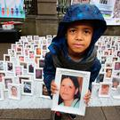 Ethan Lieghio (8) with a photo of his aunt Marsia Lieghio at the vigil at Leinster House. Photo: Tom Burke
