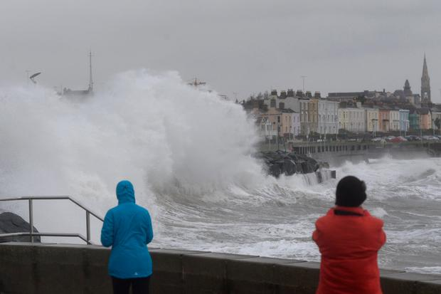 Walkers watch the big waves this month in Dún Laoghaire, Co Dublin. Photo: Justin Farrelly