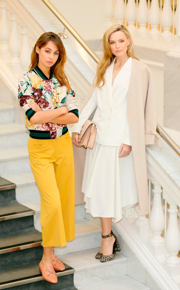 One of standout looks was an M&S Collection white blazer and waterfall skirt costing €82 and €67 respectively, pictured on Sarah (right), worn under a cream Autograph cashmere/wool mix coat, €165. Other highlights were an Autograph floral bomber, €95 and wide leg mustard trousers, €65, worn by Thalia. Photo: Kieran Harnett