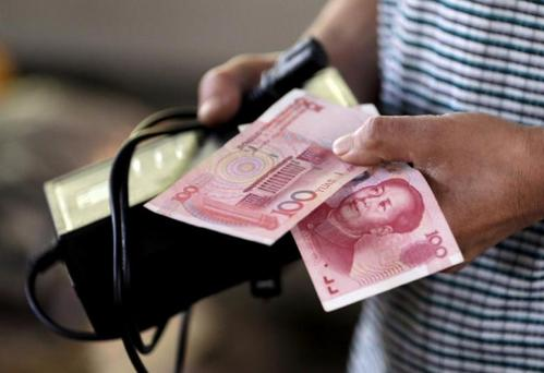 A customer holds a 100 Yuan note at a market in Beijing, August 12, 2015. REUTERS/Jason Lee/File Photo