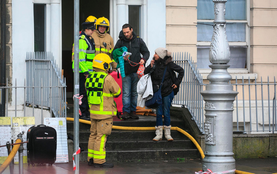 Members of the public with Dublin Fire Brigade crew following a fire at a building on Mountjoy Square Picture: Collins Dublin