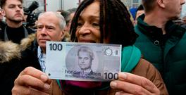 A woman holds a fake hundred guilder note, the Dutch currency before the introduction of the euro, baring the portrait of Geert Wilders during an election campaign stop in Spijkenisse, near Rotterdam Picture: AP