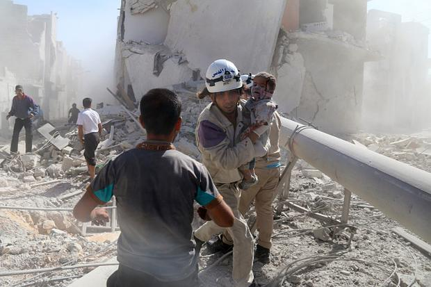 An emergency responder carries a wounded child following a reported barrel bomb strike by government forces on a rebel-controlled district of the northern city of Aleppo on September 20, 2014. (Photo credit: KHALED KHATIB/AFP/Getty Images)