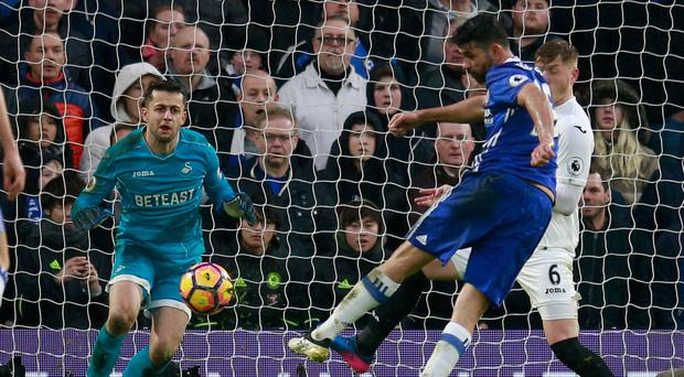Diego Costa lashes the ball home emphatically to score Chelsea's third goal of the game against Swansea. Photo: Reuters